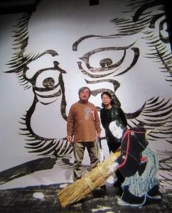 展覧会場の大だるま絵の前で記念撮影