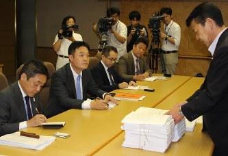 伊豆メガソーラーパークの朴代表(卓上左から2人目)に反対署名の束を示し、事業の白紙撤回を求める小野市長(右端)=伊東市役所で