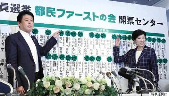 東京都議会議員選挙で大勝し、当選確実の花が付いた候補者名ボードの前で笑顔を見せる地域政党「都民ファーストの会」代表の小池百合子知事(右)と野田数幹事長=2日夜、東京都新宿区の同党開票センター