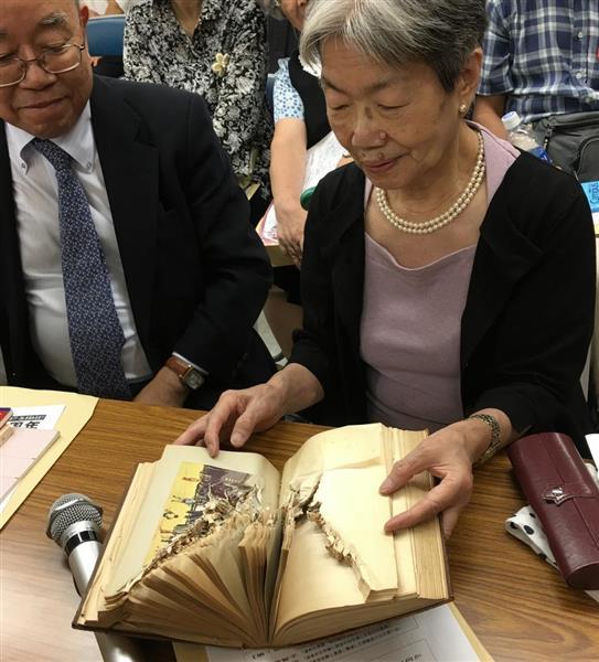 通州事件で、弾丸を受けて破損した父の遺品の日記帳を開く加納満智子さん(右)=29日、東京都千代田区(原川貴郎撮影)。200人以上の日本人居留民が中国人部隊などに虐殺された…「通州事件」から80年、集会
