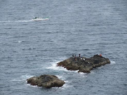 18 釣り人と沖を行く漁船