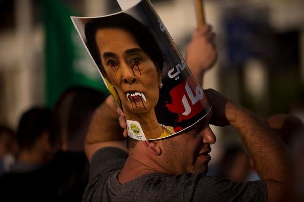 wor1709140047-p1_11日、イスラエル・テルアビブのミャンマー大使館前で、スーチー氏の顔に落書きを加えた写真を掲げ、ミャンマーのロヒンギャ問題対応に抗議する男性(AP)