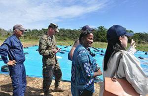 d848b7bf9370e77202fe0米軍ヘリ炎上事故の現場で沖縄防衛局から説明を受ける米軍の補償担当者(右から2人目)と、地主の西銘晃さん(左端)ら