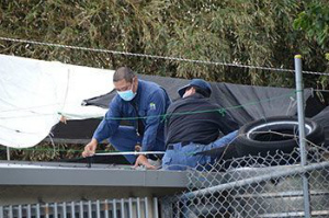 85d0b9e436b313a7754c米軍ヘリの部品が見つかった保育園の屋根を調べる県警職員ら