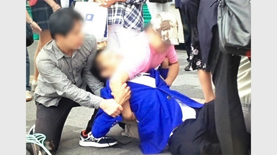 取り押さえられ、青いブレザーを着ているのが、亀岡容疑者(読者提供。画像は一部加工)。