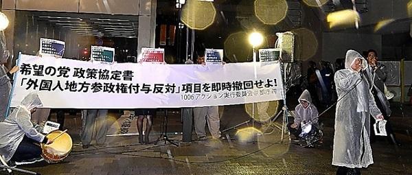 雨の中、希望の党の「外国人参政権反対」協定に抗議する人たち=6日午後6時42分、東京都新宿区の都庁前、迫和義撮影