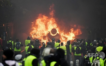 パリで炎を上げる車の前に集まったデモ参加者_2018年12月1日撮影