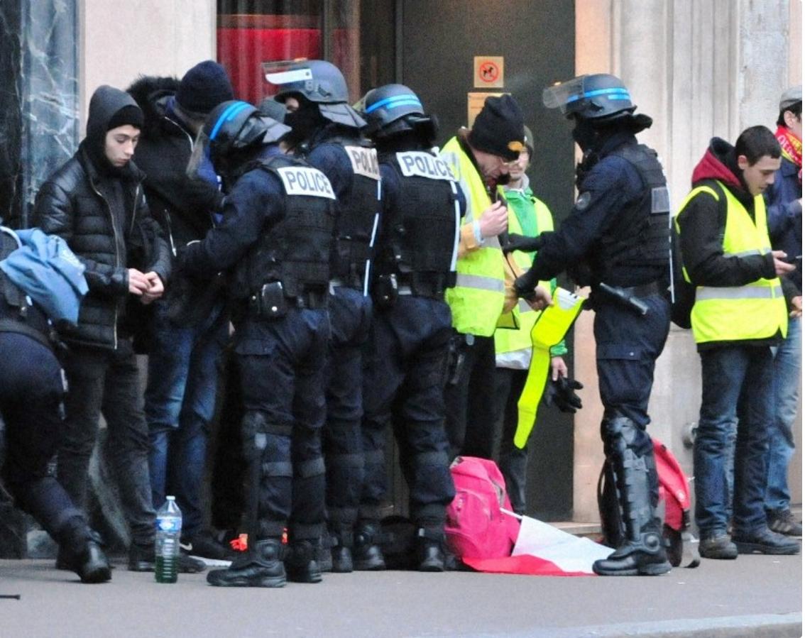 パリにてデモ参加者の身元と所持品を確認する警察官