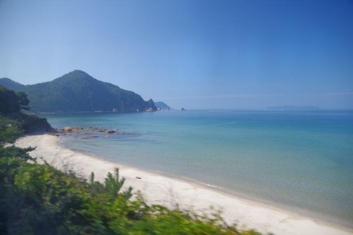 車窓から白い砂浜と青い海