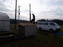 【写真】大工さんが井戸小屋の屋根にあがって修理している様子