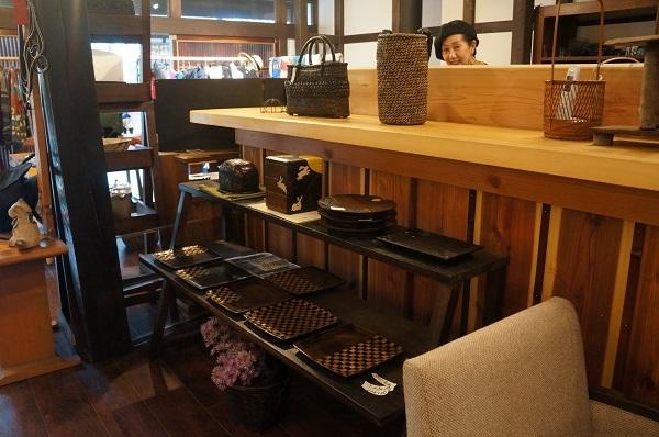 『シーズ藤原家』オーナーの藤原しのぶさん、お気に入りの木地製品の前で